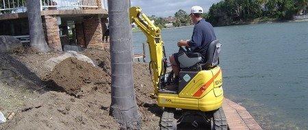 man operating yellow mini excavator