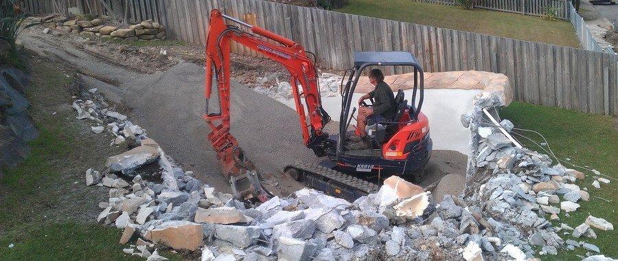 man operating orange excavator in demolished area