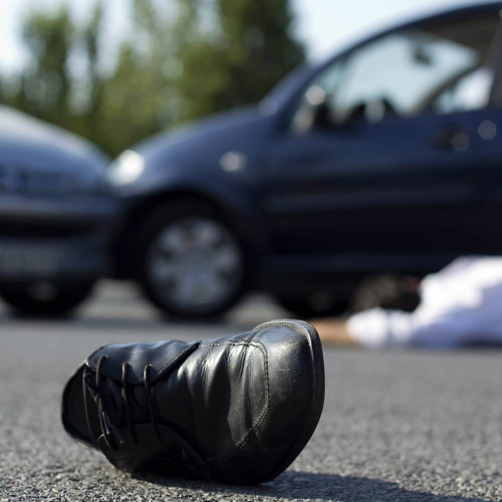 A man lying on the road after a car accident