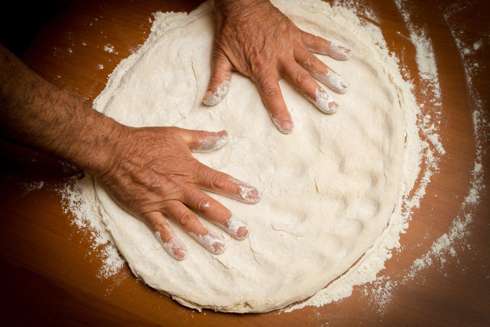 pizzaiolo durante fase di preparazione di pasata per la pizza