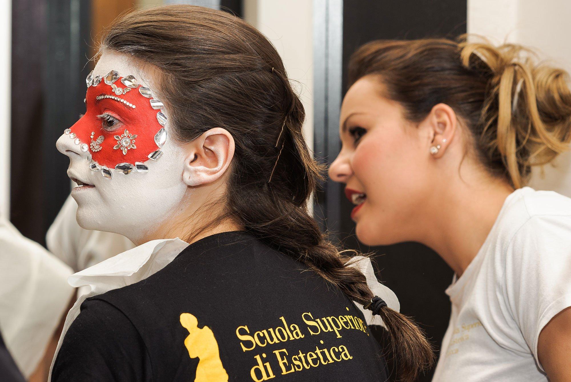 Due ragazze, di cui una con una pittura facciale bianca e rossa