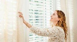 donna apre le tende vicino una finestra