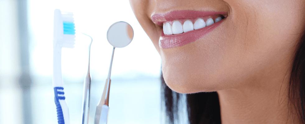 spazzolino,specchietto, rampino e una donna sorridente