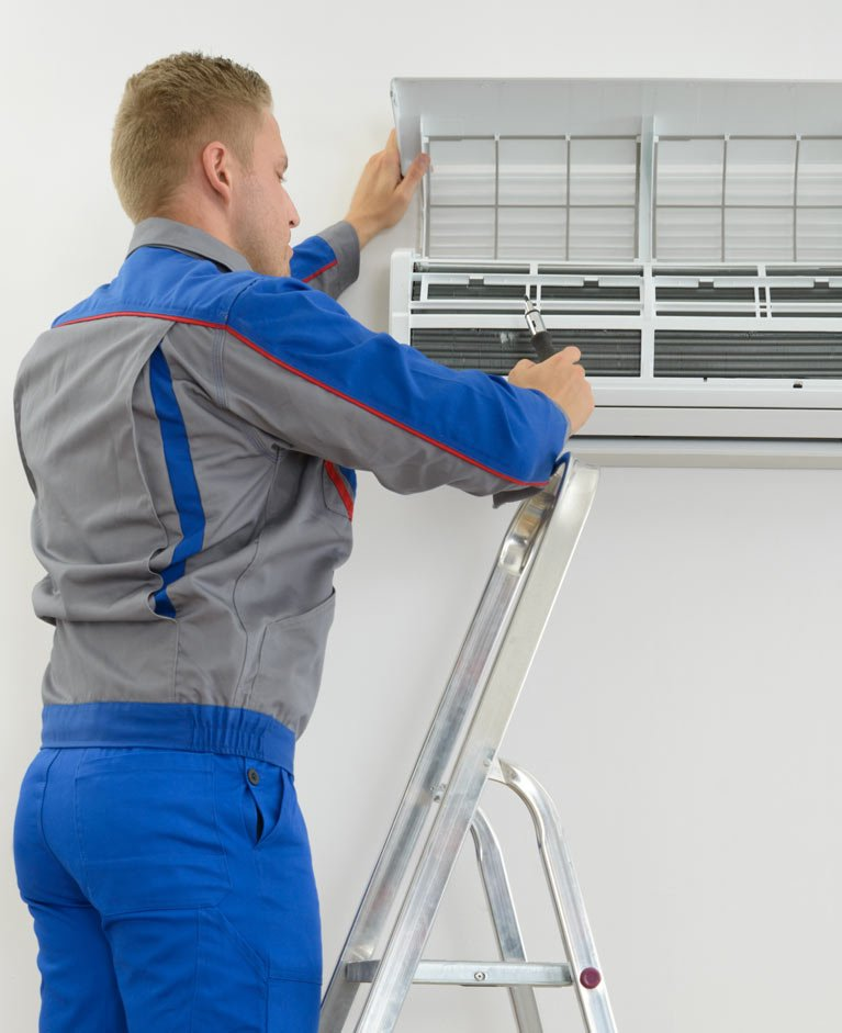 Technician doing air conditioning installation in a Canberra home