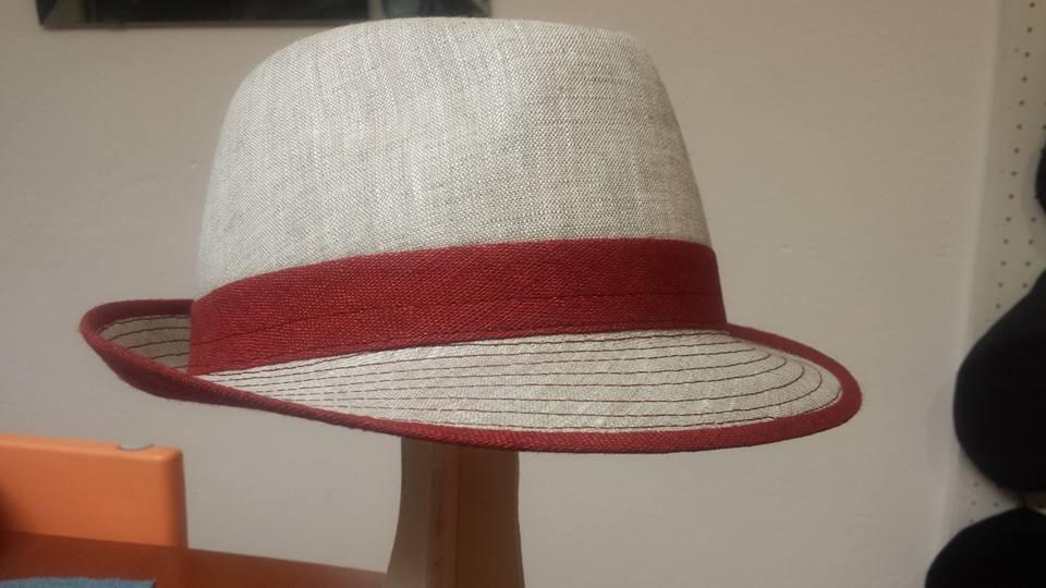 Un cappello a borsalino di color beige e rosso