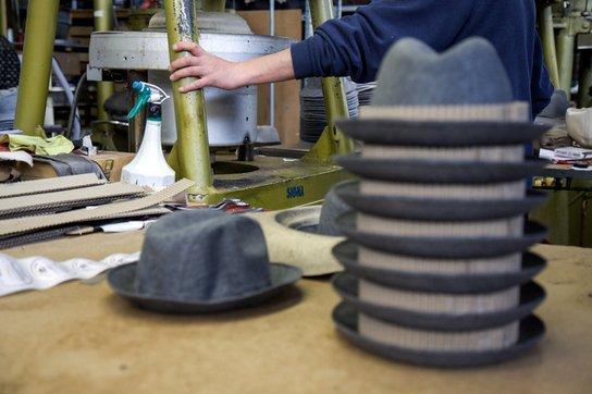 Una insieme di cappelli di color grigio e dietro un uomo mentre lavora con dei macchinari