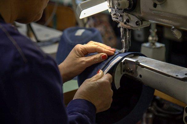 Una donna mentre lavora con un macchinario per cucire capellini