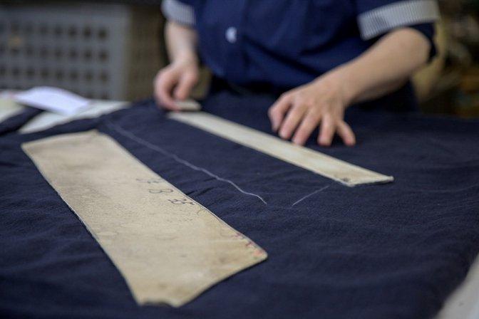 Una donna mentre sta prendendo le misure su un telo di color blu