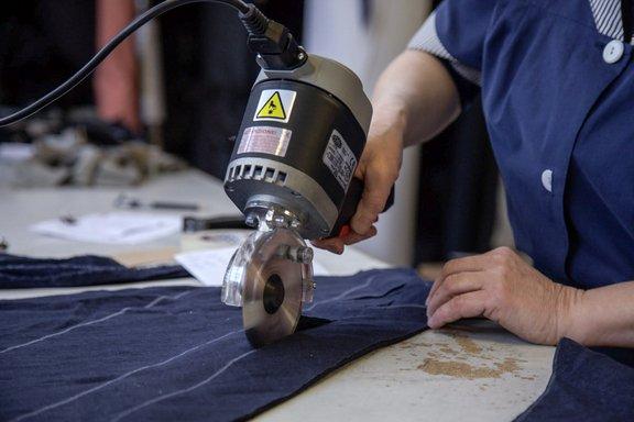 Una donna mentre sta tagliando un telo con un flessibile con un disco da taglio