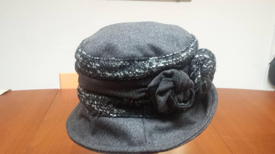 Un cappello da donna di color grigio con dei fiorellini di color grigio e nero