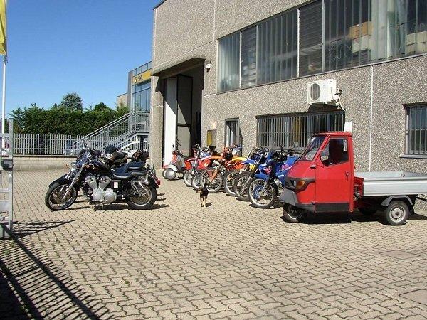delle moto e un Ape car parcheggiate fuori da un officina