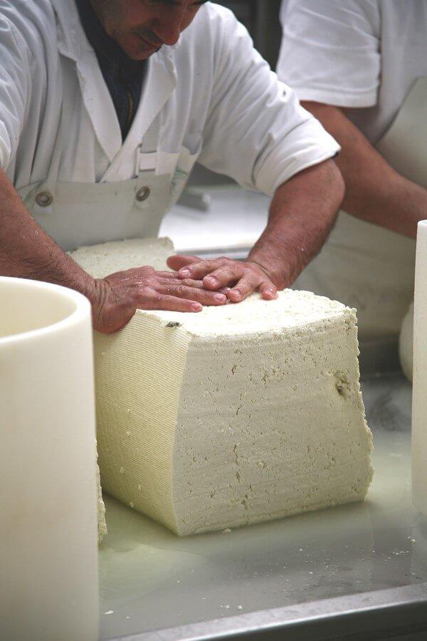 uomo mentre lavora una forma di formaggio