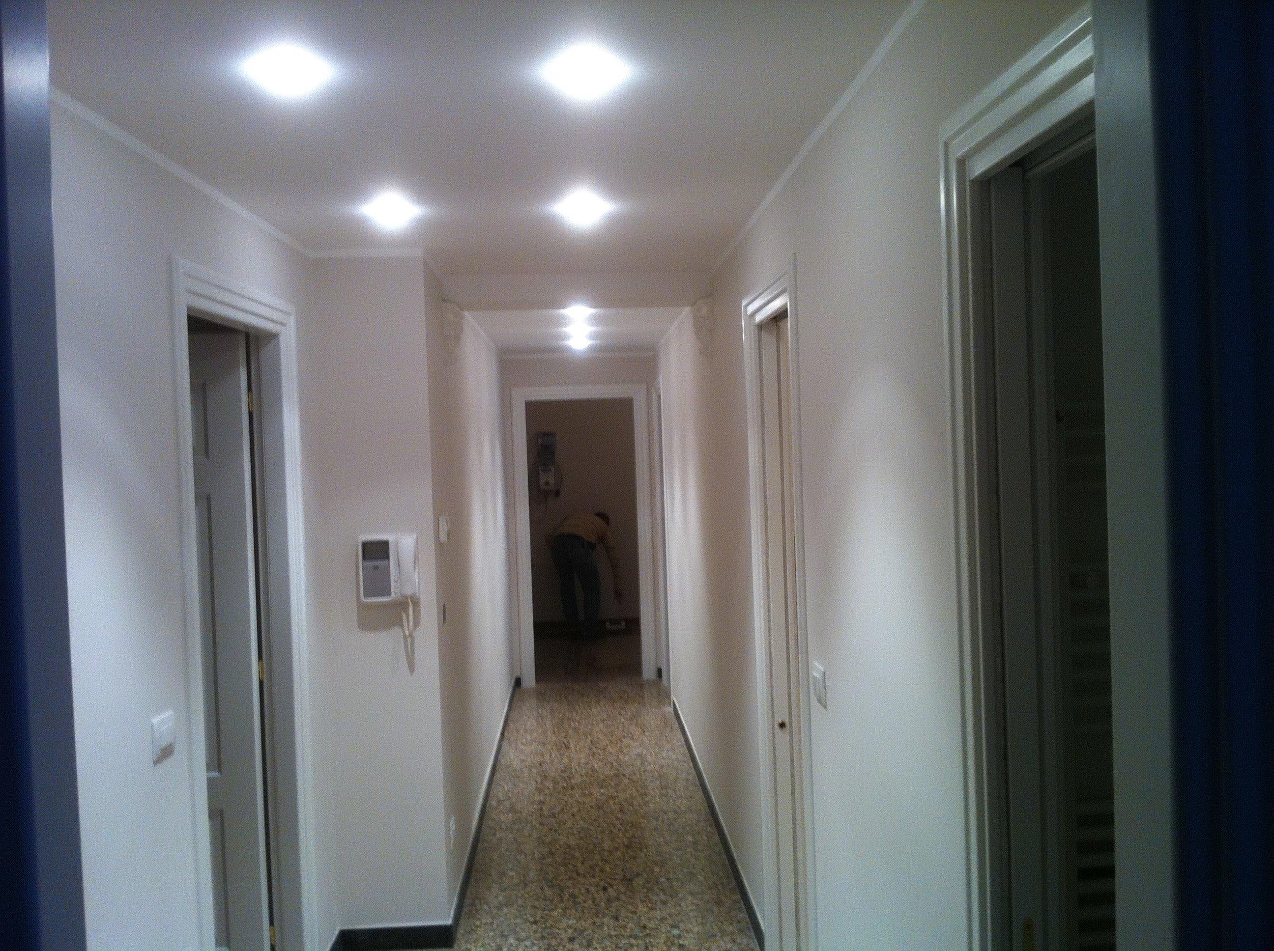 Corridoio interno con pareti bianche e controsoffitto illuminato