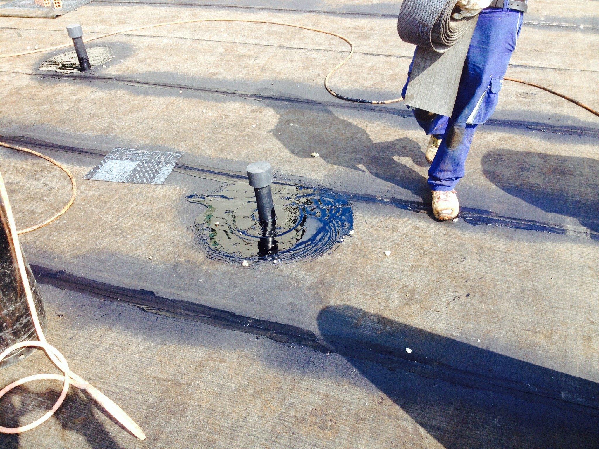 Operaio su un tetto trasporta un rullo di rivestimenti impermeabilizzanti