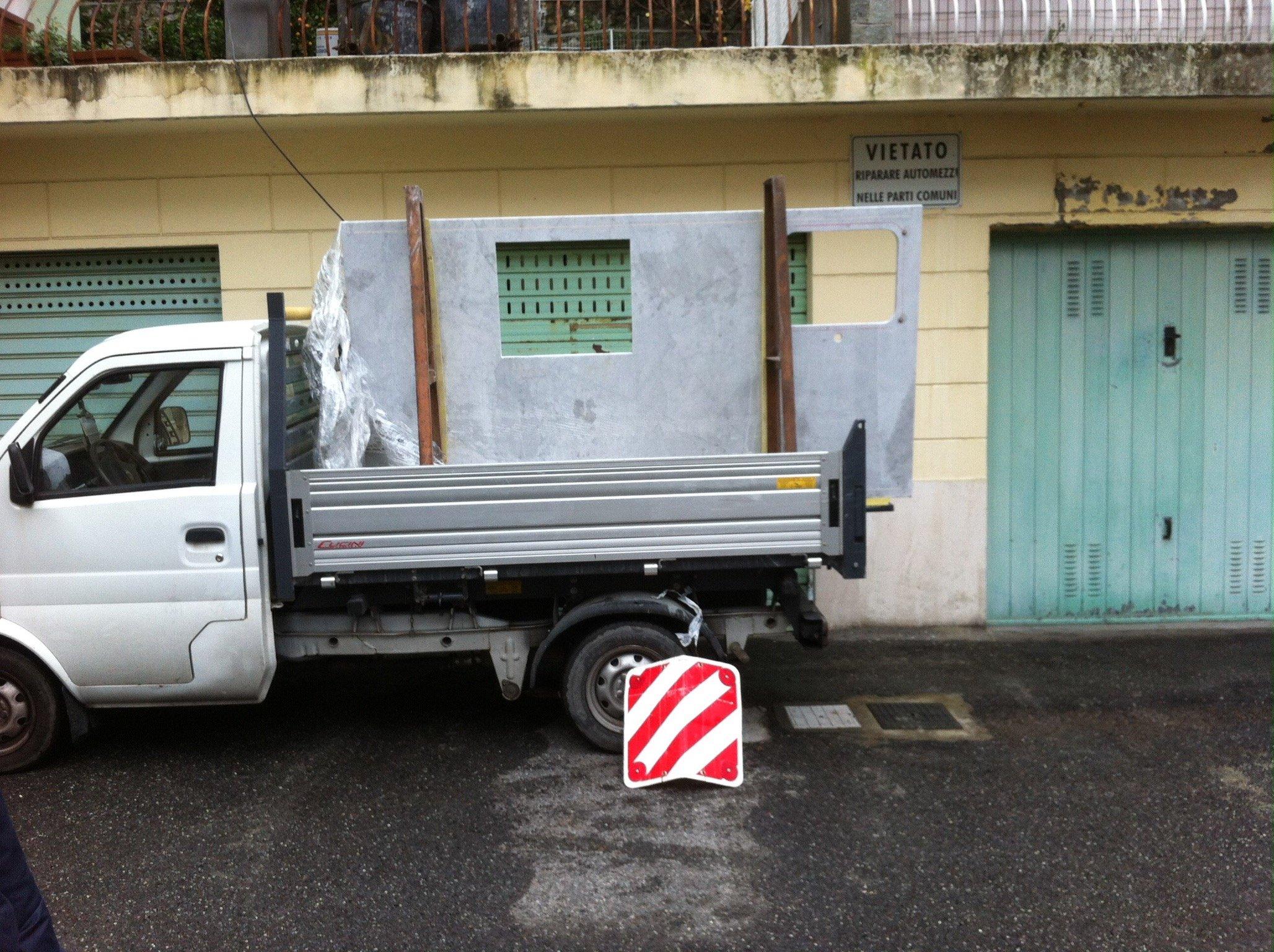 Parete con finestre trasportata da un furgoncino con cassone