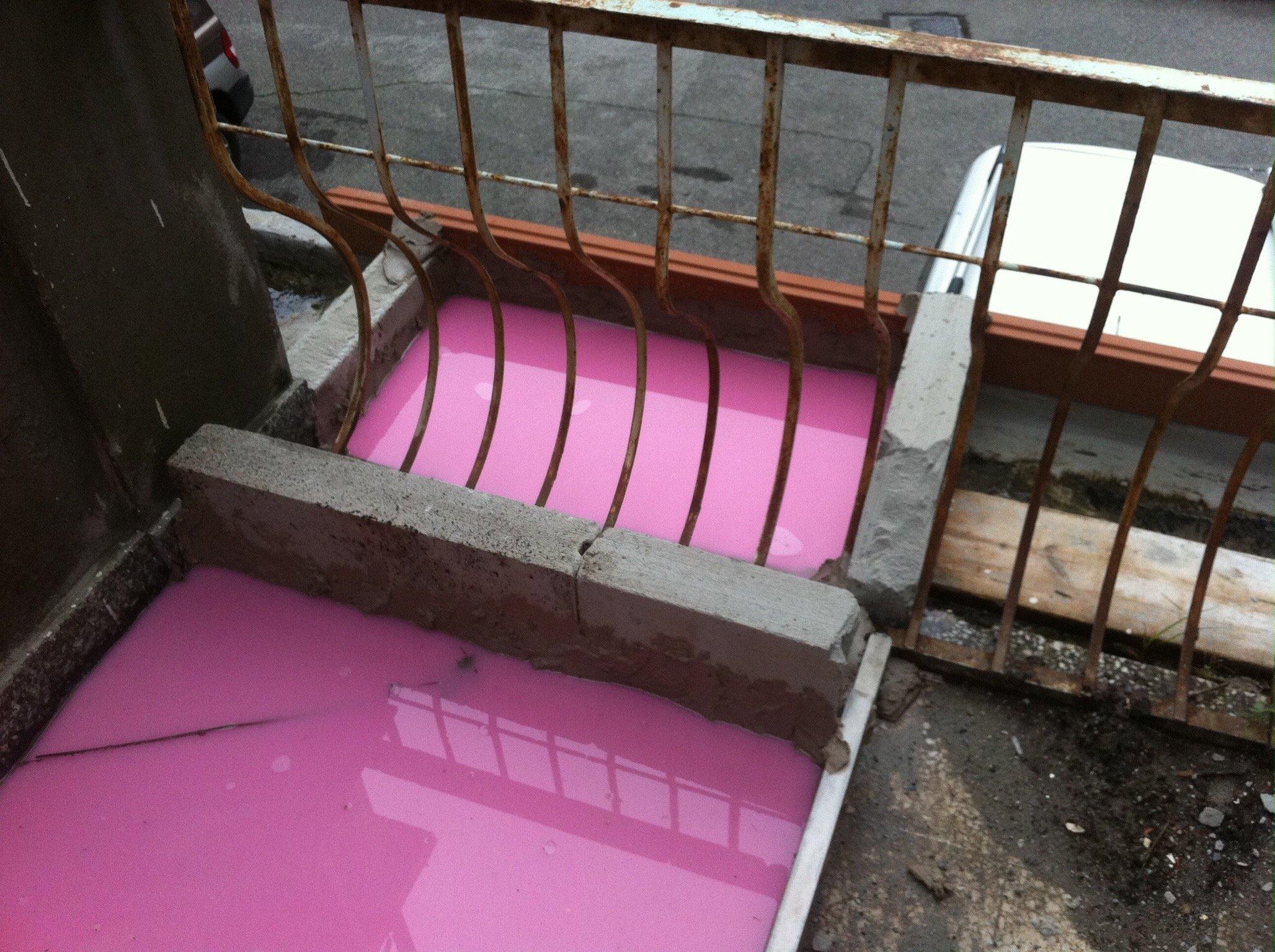Ringhiera di un balcone; sotto una canaletta con del liquido rosa