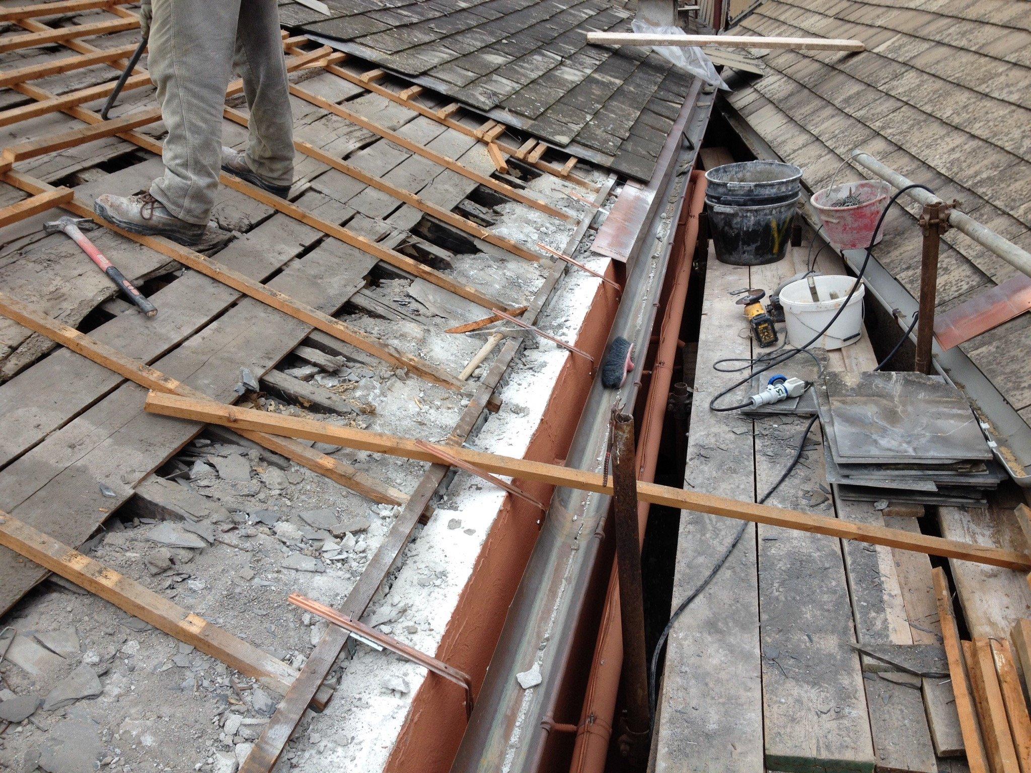 Operaio in piedi su una copertura in fase di lavorazione
