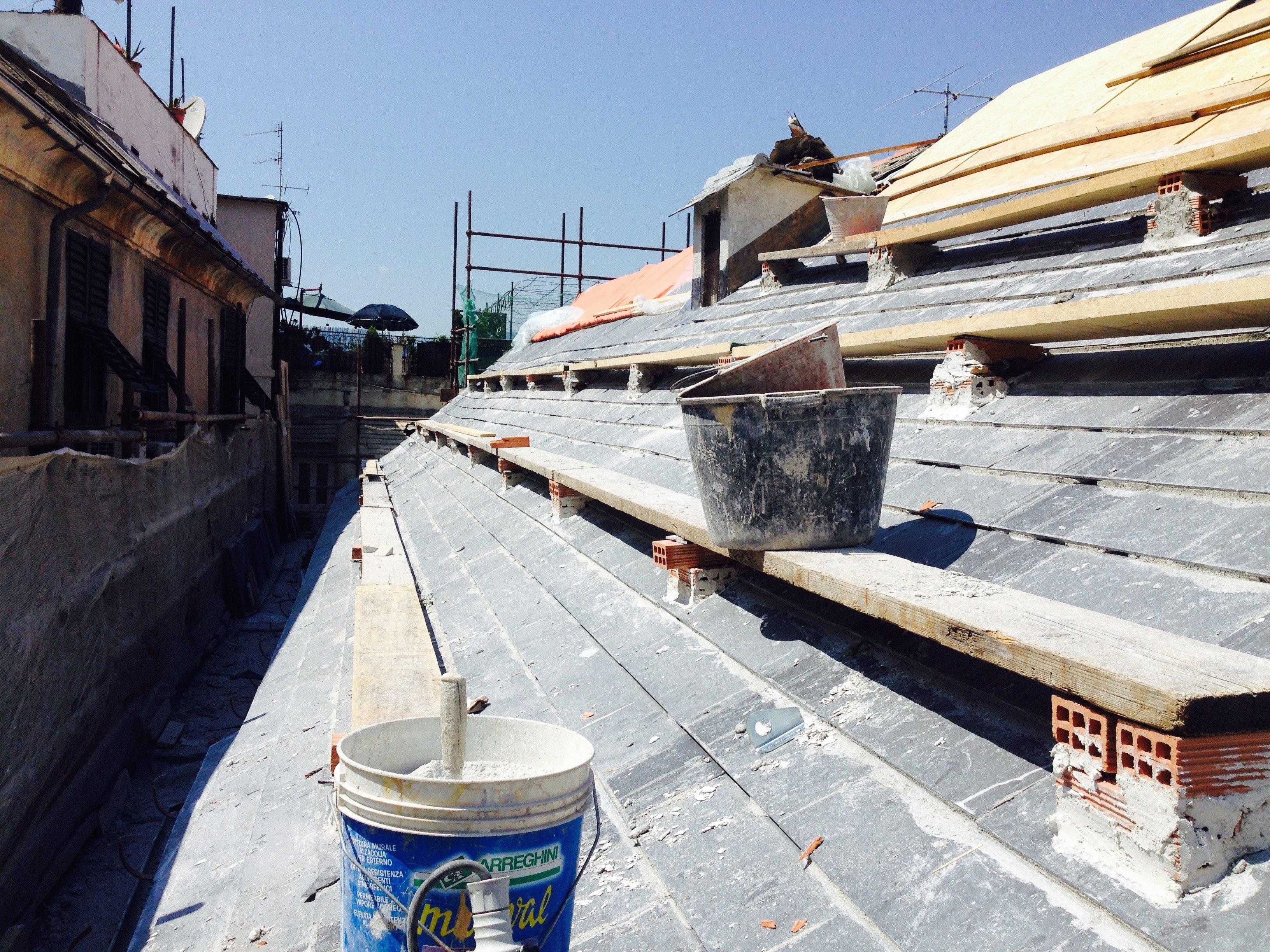 Un secchio e una caldarella poggiate su una copertura in fase di realizzazione