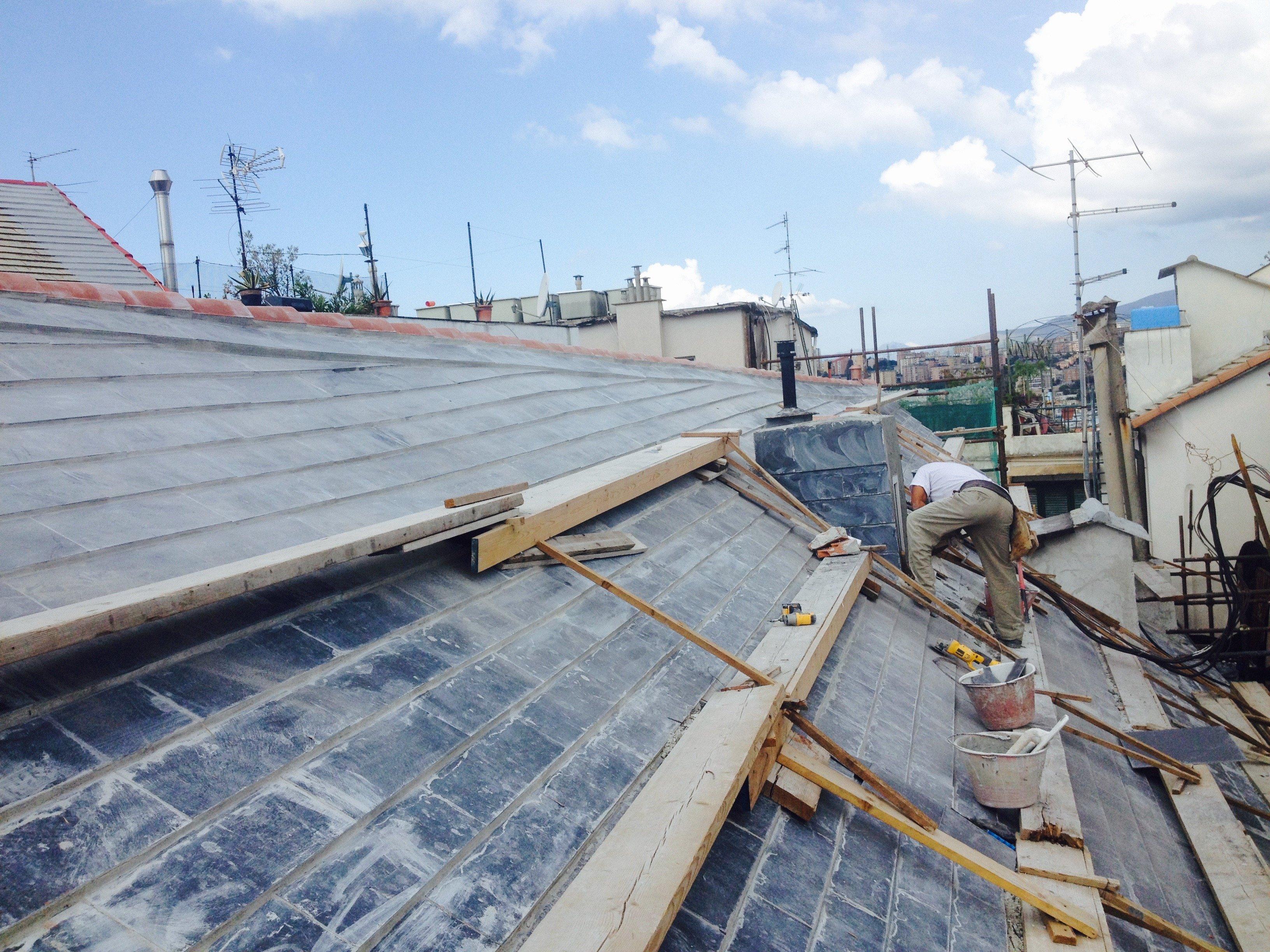 Operaio al lavoro sul rifacimento di un tetto