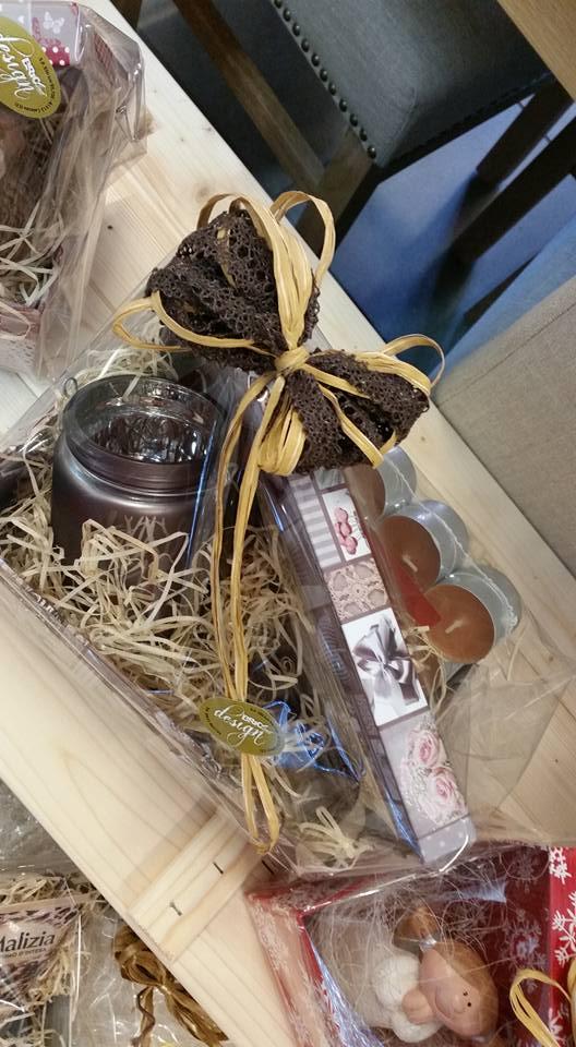 un cestino con dei filamenti di paglia,delle candele un barattolo e un fiocco marrone
