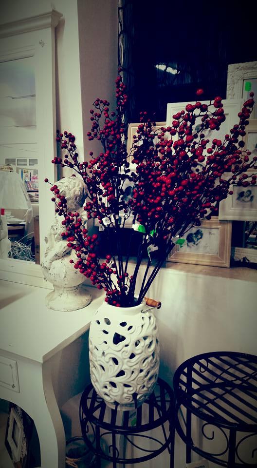 un vaso bianco con dentro dei rami con delle bacche rosse artificiali