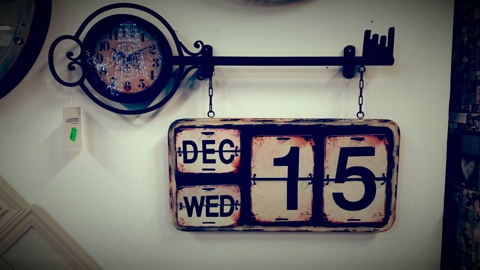 un orologio da muro a forma di chiave e sotto un cartello che funge da calendario