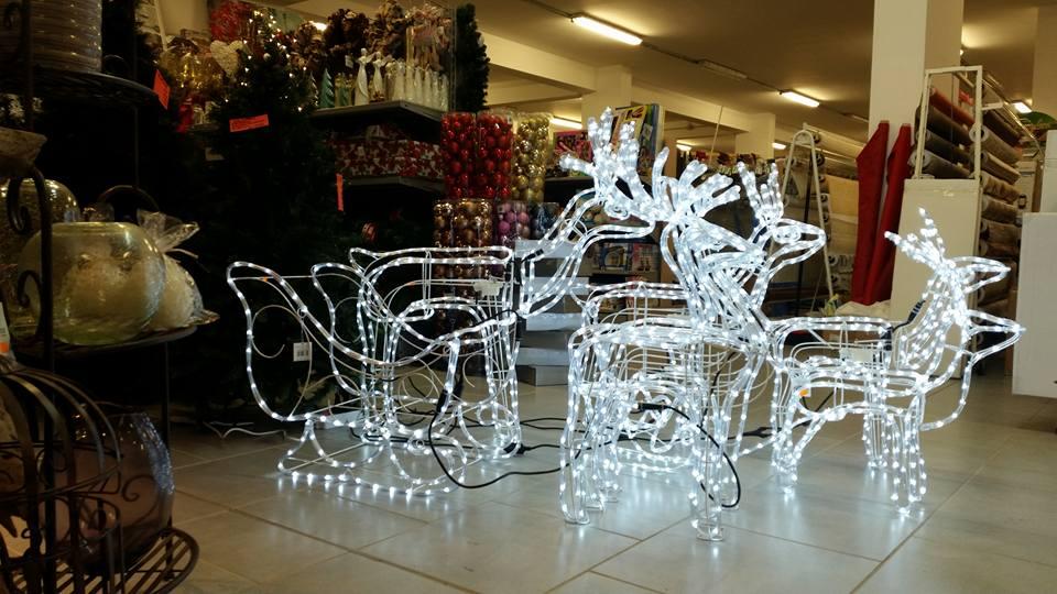 delle renne luminose e accanto altre decorazioni natalizie in un negozio