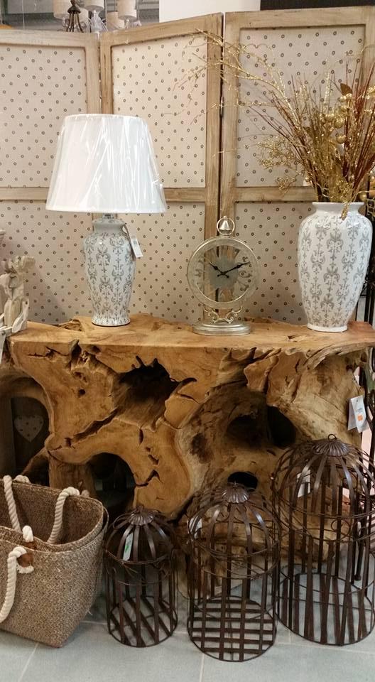 delle gabbie da uccelli color marrone, un tavolo a forma di tronco d'albero con sopra dei vasi con delle piante artificiali e un orologio