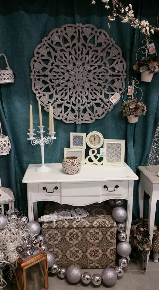 un tavolino bianco con sopra delle cornici,un oriologio,un candeliere e altri oggetti sotto e appesi al muro