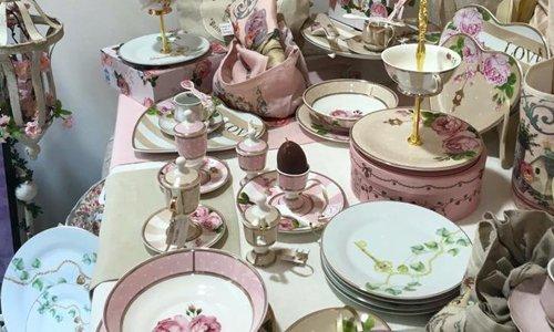 una tavola con dei piatti bianchi e rosa