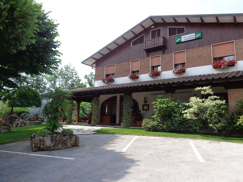 Il ristorante visto da fuori con un parcheggio e un giardino con degli alberi