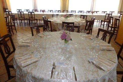 Il tavolo rotondo apparecchiato e delle sedie in legno