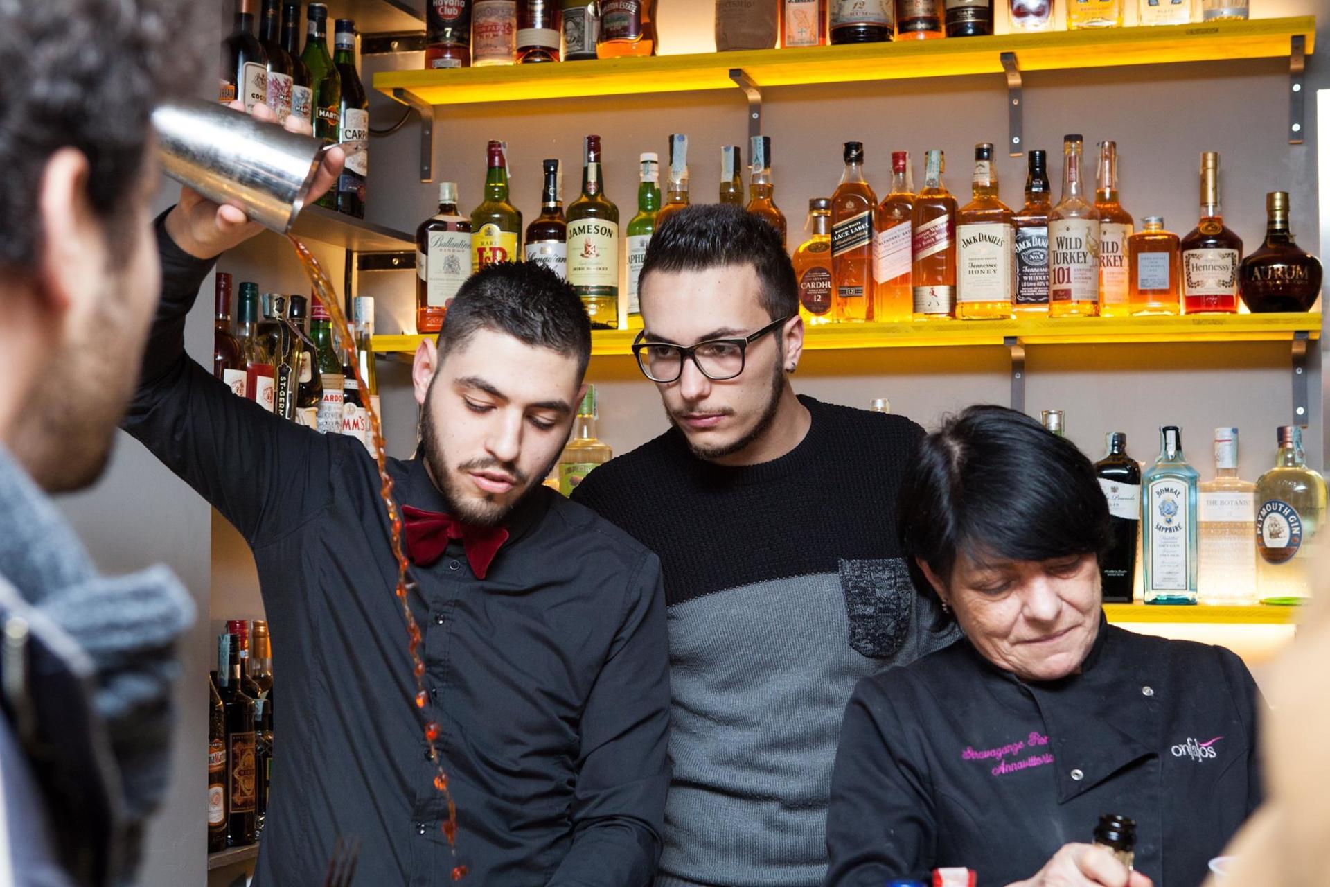 un uomo mentre versa vino da un bicchiere con ragazzi in un bar