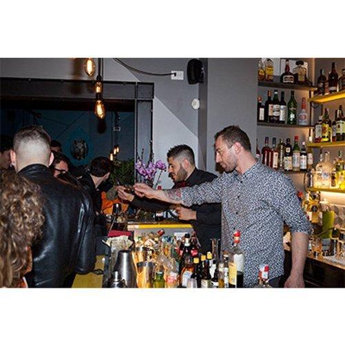 gente in un bar con vini