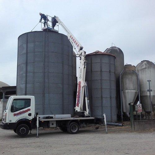 un camion con una piattaforma aerea e un uomo su un silos