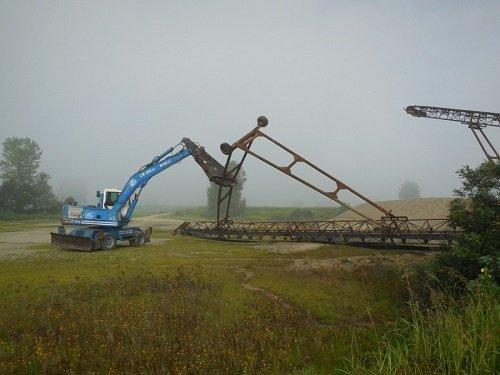 una demolitrice al lavoro su delle strutture di ferro in un prato