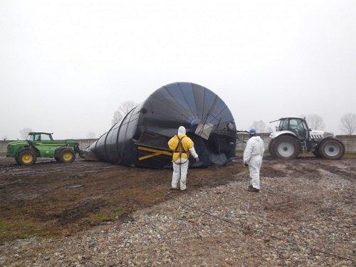 due uomini con delle tute protettive  e un silos a terra
