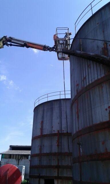 un uomo su una piattaforma aerea vicino a un silos