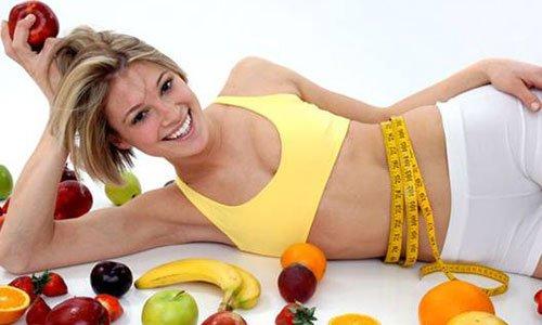 una ragazza bionda sdraiata di lato con un top giallo un metro giallo di gomma arrotolato alla vita e intorno a lei della frutta