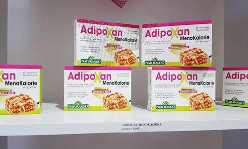 delle confezioni bianche e rosa con scritto AdipoXan