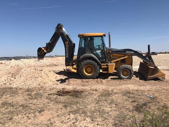 back hoe digging in oilfield