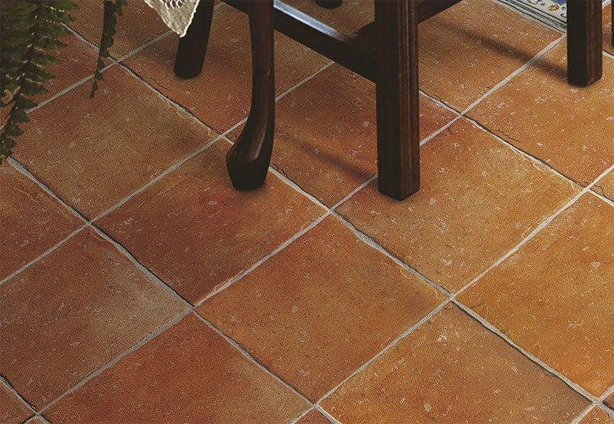 un pavimento di piastrelle arancioni e delle gambe di una sedia