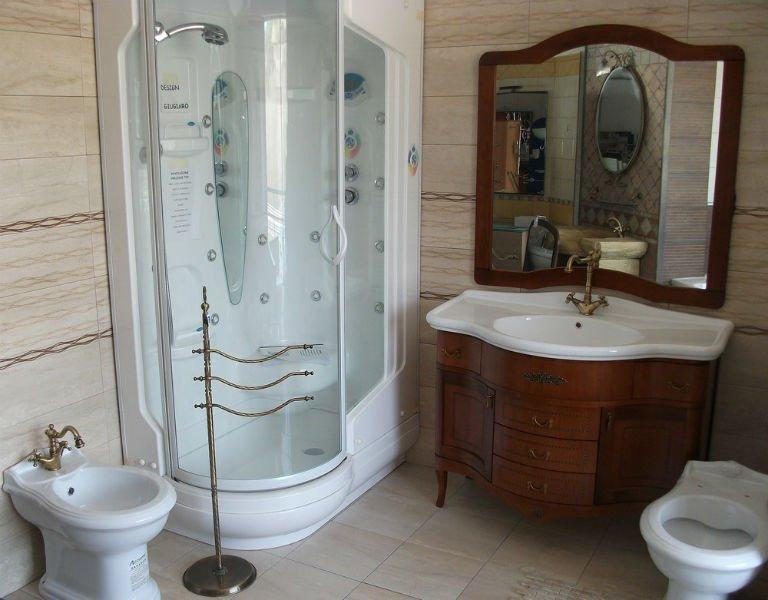 un bagno con un box doccia moderno, bidet e un mobile in legno con un lavabo