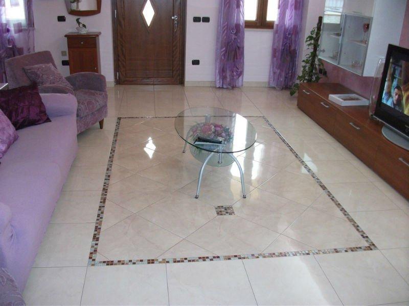 un pavimento in marmo beige a disegni e un tavolino di vetro