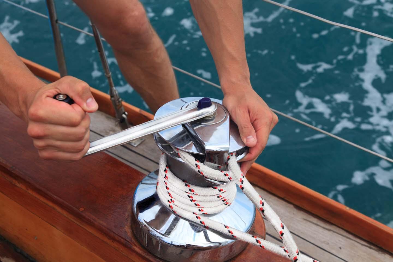 Skipper di un'imbarcazione slega la corda dalla galloccia