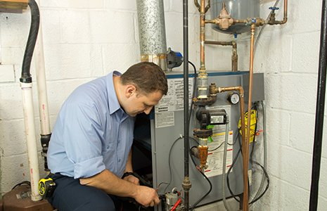 Plumber fixing gas furnace in High Point