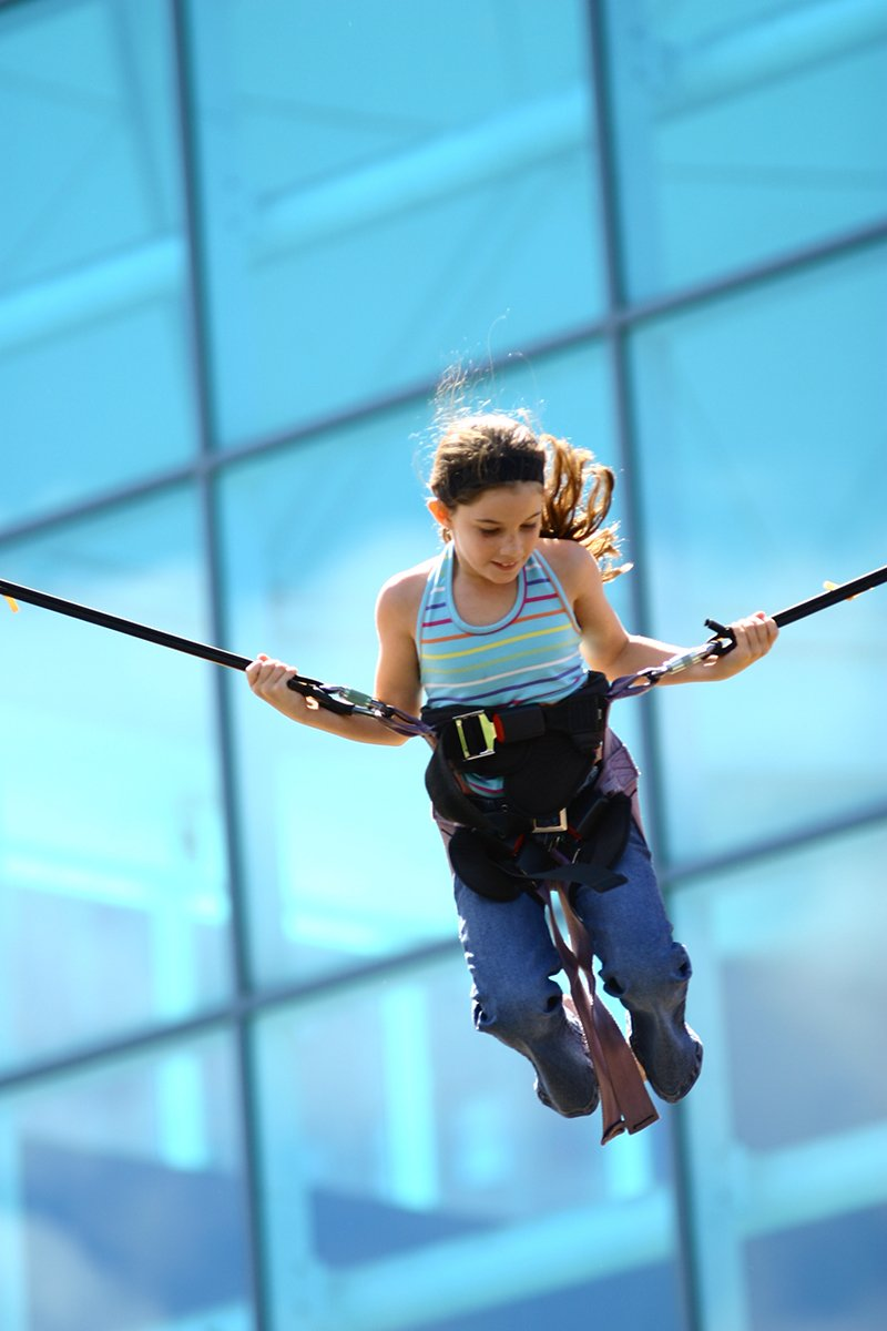 Young girl having fun with bungee trampoline