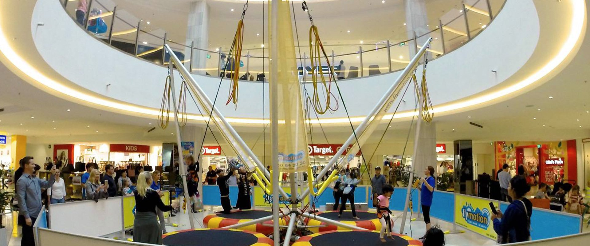 Children enjoying the bungee trampoline in the mall