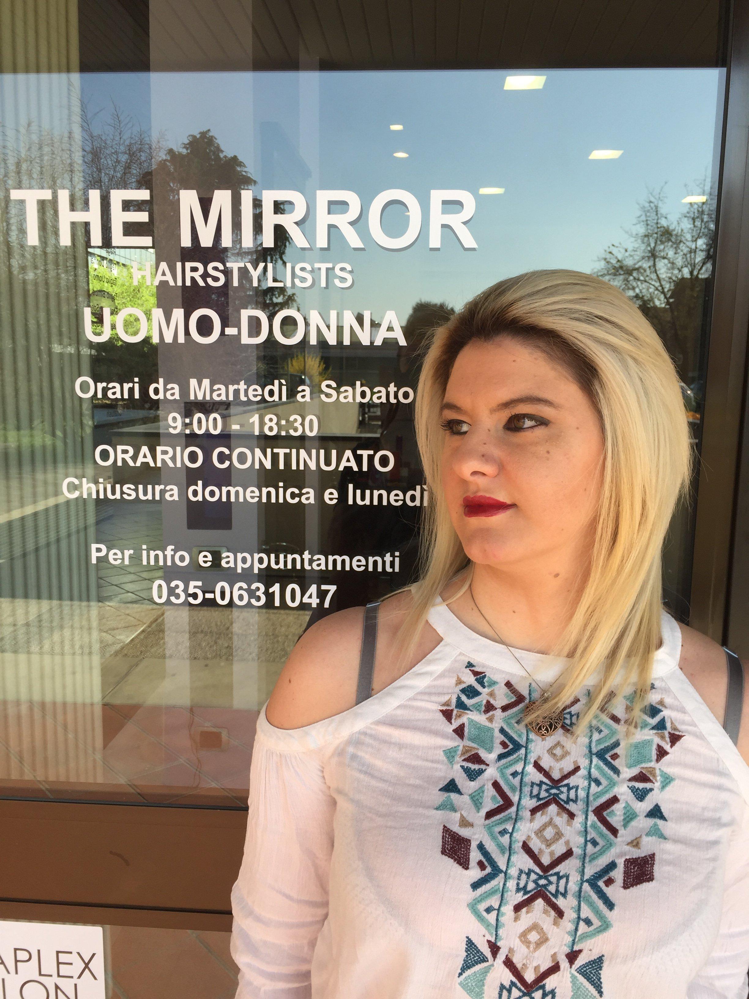 una ragazza di fronte al The Mirror Hairstylist
