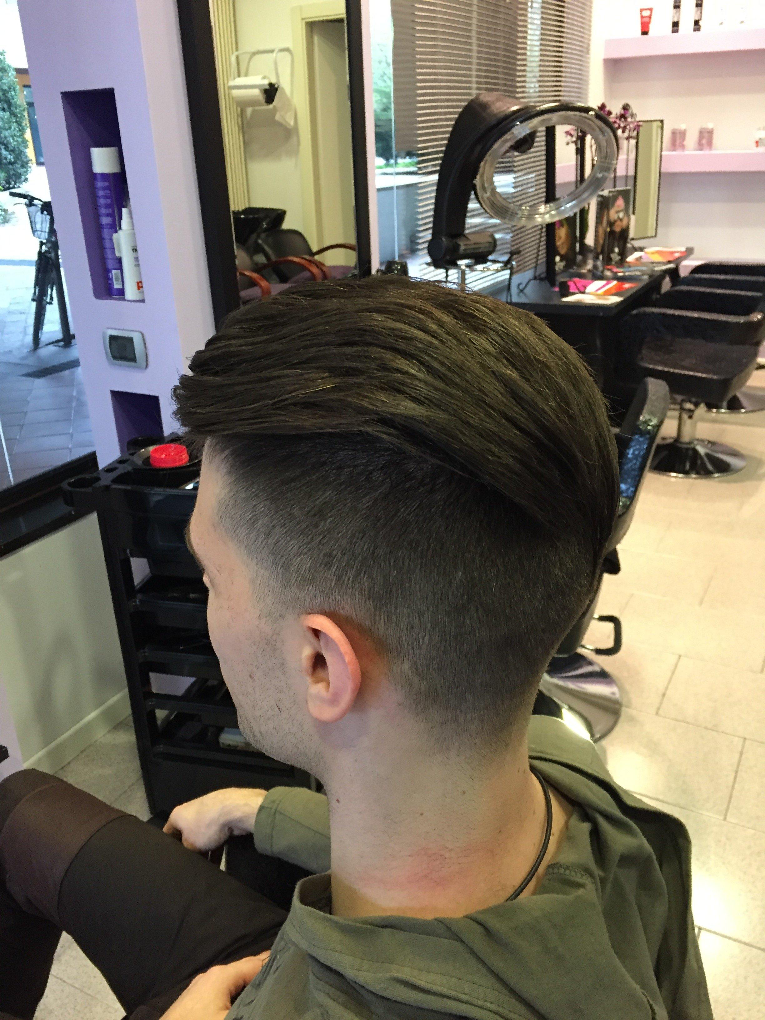 un ragazzo con capelli rasati ai lati e sopra lunghi